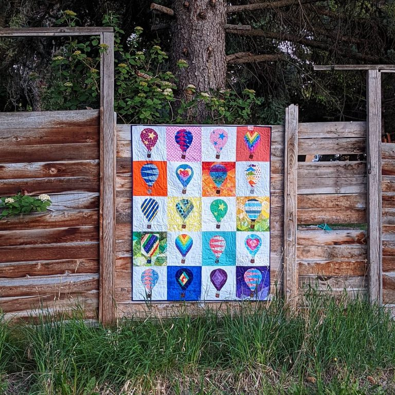 Quilt hanging on a wooden fence using the Rise Above quilt blocks